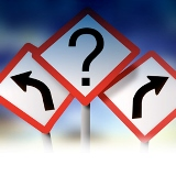 Road direction signs with arrows and question mark.Sky background.
